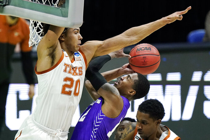 Texas' Jericho Sims (20) blocks the path of Abilene Christian's Mahki Morris during the first half of a college basketball game in the first round of the NCAA tournament at Lucas Oil Stadium in Indianapolis Saturday, March 20, 2021. (AP Photo/Mark Humphrey)