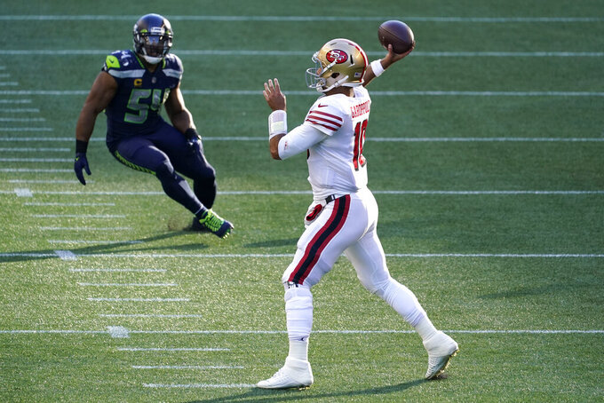 San Francisco 49ers quarterback Jimmy Garoppolo, right, passes as Seattle Seahawks middle linebacker Bobby Wagner (54) looks on at left, during the first half of an NFL football game, Sunday, Nov. 1, 2020, in Seattle. (AP Photo/Elaine Thompson)