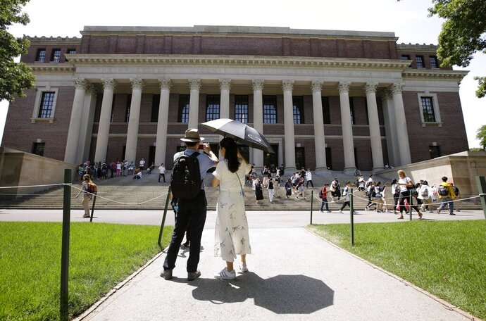 FILE - In this July 16, 2019, file photo, people stop to record images of Widener Library on the campus of Harvard University in Cambridge, Mass. A federal appeals court will hear arguments Wednesday, Sept. 16, 2020, in a lawsuit alleging that Harvard illegally discriminates against Asian Americans in its admissions process. The plaintiff appealed after a federal judge ruled in favor of Harvard in 2019. (AP Photo/Steven Senne, File)