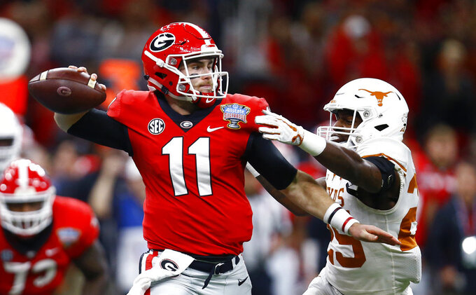 Georgia quarterback Jake Fromm (11) passes under pressure from Texas defensive back B.J. Foster (25) during the first half of the Sugar Bowl NCAA college football game in New Orleans, Tuesday, Jan. 1, 2019. (AP Photo/Butch Dill)