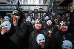 Masked pro-democracy protesters march on a street in Hong Kong, Sunday, Dec. 8, 2019. Marchers are again expected to fill Hong Kong streets Sunday in a rally that will test the enduring appeal of an anti-government movement marking a half year of demonstrations. (AP Photo/Mark Schiefelbein)