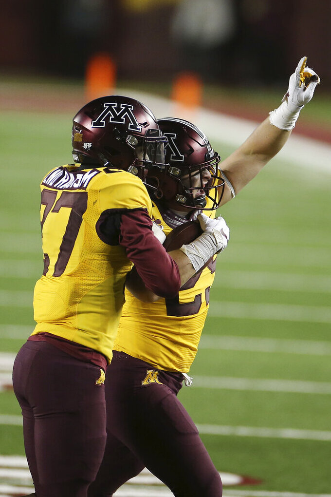 Minnesota linebacker Josh Aune (29) holds the ball and celebrates with defensive back Tyler Nubin (27) after Aune intercepted a Purdue pass during the second half of an NCAA college football game Friday, Nov. 20, 2020, in Minneapolis. Minnesota won 34-31. (AP Photo/Stacy Bengs)