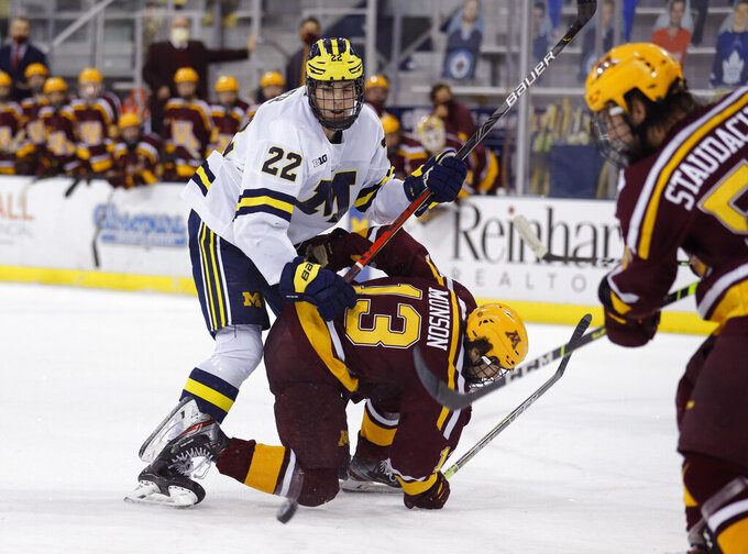 FILE - In this Dec. 8, 2020, file photo, Michigan's Owen Power (22) watches the puck while working against Minnesota's Cullen Munson (13) during an NCAA hockey game in Ann Arbor, Mich. The NHL Central Scouting Bureau has three Michigan players listed among its top six North American prospects, led by 6-foot-6 defenseman Power, the top-ranked player, who is current representing Canada at the World Hockey championships in Latvia. (AP Photo/Al Goldis, File)