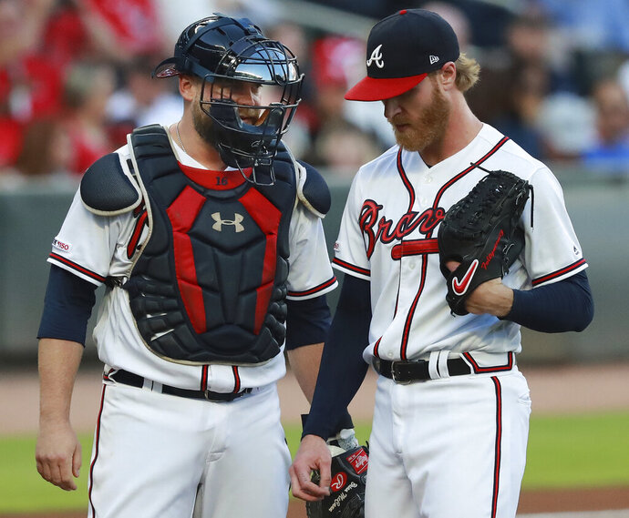 Atlanta Braves catcher Brian McCann confers with pitcher Mike Foltynewicz, who had given up a three-run home run to St. Louis Cardinals' Marcell Ozuna during the first inning of a baseball game Tuesday, May 14, 2019, in Atlanta. (Curtis Compton/Atlanta Journal-Constitution via AP)