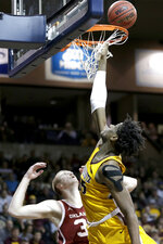 Minnesota's Daniel Oturu, right, scores a basket against Oklahoma's Brady Manek (35) during the second half of an NCAA college basketball game in Sioux Falls, S.D., Saturday, Nov. 9, 2019. Oklahoma won 71-62. (AP Photo/Nati Harnik)