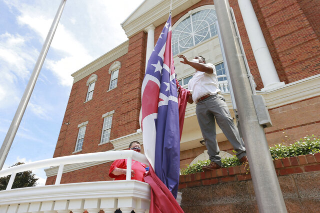 City of Tupelo Community Outreach Coordinator Marcus Gary takes down the State Flag of Mississippi that flew over the City Hall of Tupelo one last time Monday, June 29, 2020.Mississippi is retiring the last state flag in the U.S. that includes the Confederate battle emblem. (Thomas Wells/Northeast Mississippi Daily Journal, Via AP)
