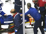 Toronto Maple Leafs defenseman Jake Muzzin (8) leaves the ice on a stretcher while playing against the Columbus Blue Jackets during the third period of an NHL hockey playoff game  Tuesday, Aug. 4, 2020 in Toronto. (Nathan Denette/The Canadian Press via AP)