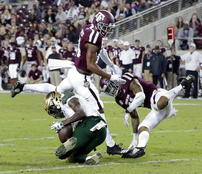UAB wide receiver Kailon Carter, left, makes the catch under pressure from Texas A&M defensive back Keldrick Carper, center, and defensive back Larry Pryor, right, during the second half of an NCAA college football game Saturday, Nov. 17, 2018, in College Station, Texas. (AP Photo/Michael Wyke)