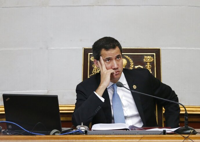 FILE - In this Oct. 1, 2019 file photo, Juan Guaido, opposition leader and self-proclaimed interim president of Venezuela, attends the weekly legislative session in Caracas, Venezuela. The U.S. Treasury Department on Thursday, Oct. 24, 2019, issued an order giving Guaido's team three months to negotiate a debt settlement. A $913 million payment due Monday could have triggered foreclosure. (AP Photo/Ariana Cubillos, File)