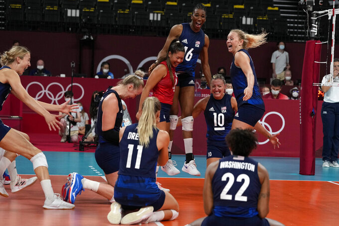 United States players celebrate winning the women's volleyball semifinal match between Serbia and United States at the 2020 Summer Olympics, Friday, Aug. 6, 2021, in Tokyo, Japan. (AP Photo/Frank Augstein)