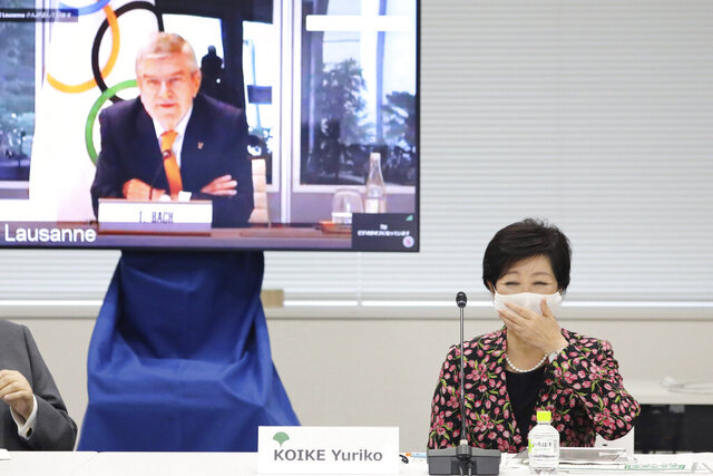 "Tokyo Gov. Yuriko Koike, right, reacts before an on-line meeting focused on how to pull off the delayed Tokyo Games, in Tokyo, Thursday, Sept. 24, 2020. IOC President Thomas Bach delivered a pep talk to Japanese government officials and local organizers on Thursday that included suggestions that ""hundreds of millions""of doses COVID-19 vaccines would be available before the postponed Olympic are to open on July 23, 2021. (Du Xiaoyi/Pool Photo via AP)"