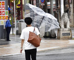 A man walks with an umbrella broken by strong winds in Naha, Okinawa, southern Japan, on Wednesday, July 21, 2021. A typhoon is forecast to bring heavy rains to Taiwan and coastal China over the weekend, days after the worst flooding on record in a central province. .(Kyodo News via AP)