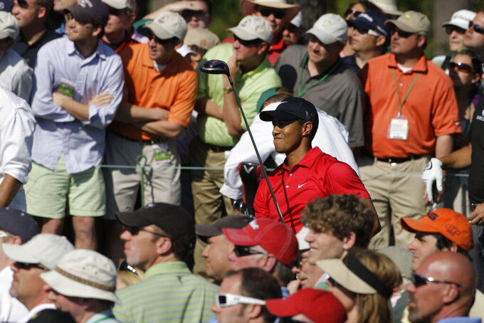 FILE - Tiger Woods is shown among spectators during the final round of the Masters golf tournament at the Augusta National Golf Club in Augusta, Ga., Sunday, April 12, 2009. Woods attracts the biggest galleries. For this Masters, there will be no spectators and no roars. (AP Photo/Morry Gash, File)