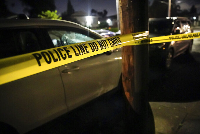 FILE - In this June 6, 2021, file photo, police respond to a multiple fatality shooting in a house in Portland, Ore. The city has seen a spike in gun violence in the past year and authorities say one reason is an increase in gang activity. (Mark Graves/The Oregonian via AP, File)