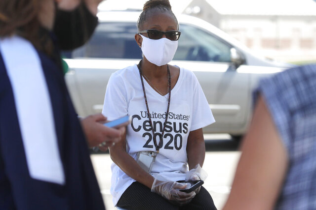 Amid concerns of the spread of COVID-19, census worker Jennifer Pope wears a mask and sits by ready to help at a U.S. Census walk-up counting site set up for Hunt County in Greenville, Texas, Friday, July 31, 2020. (AP Photo/LM Otero)
