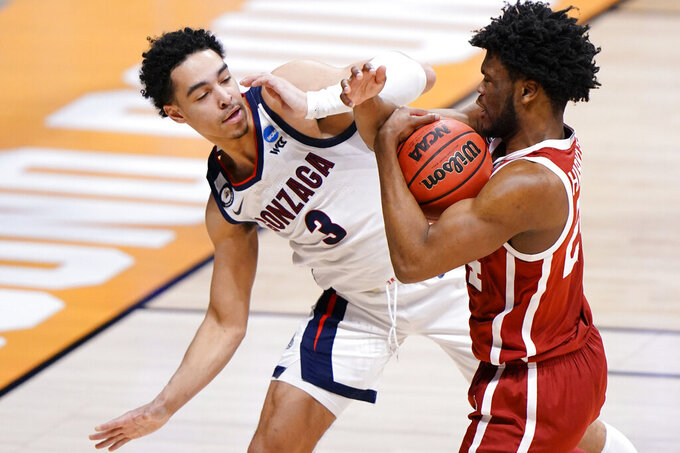 Gonzaga guard Andrew Nembhard (3) fights for a rebound with Oklahoma guard Elijah Harkless (24) in the first half of a college basketball game in the second round of the NCAA tournament at Hinkle Fieldhouse in Indianapolis, Monday, March 22, 2021. (AP Photo/AJ Mast)