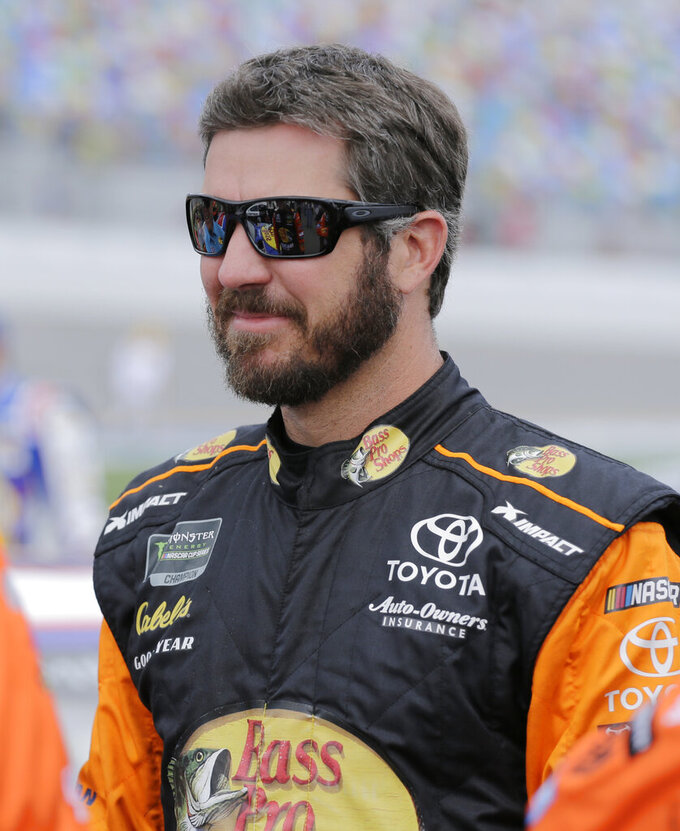 Martin Truex Jr. stands on pit road before a NASCAR auto race at Daytona International Speedway on Sunday, July 7, 2019, in Daytona Beach, Fla. (AP Photo/Terry Renna)