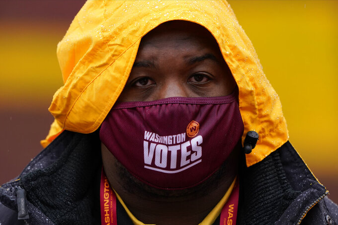 Stadium employee Marlowel Matthews wears his face mask before the start of an NFL football game between the Dallas Cowboys and Washington Football Team, Sunday, Oct. 25, 2020, in Landover, Md. (AP Photo/Susan Walsh)