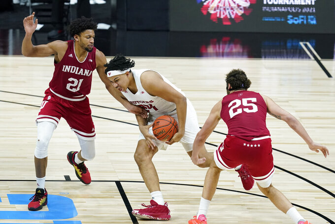 Rutgers' Ron Harper Jr. (24) goes to the basket against Indiana's Jerome Hunter (21) and Race Thompson (25) during the second half of an NCAA college basketball game at the Big Ten Conference tournament, Thursday, March 11, 2021, in Indianapolis. (AP Photo/Darron Cummings)