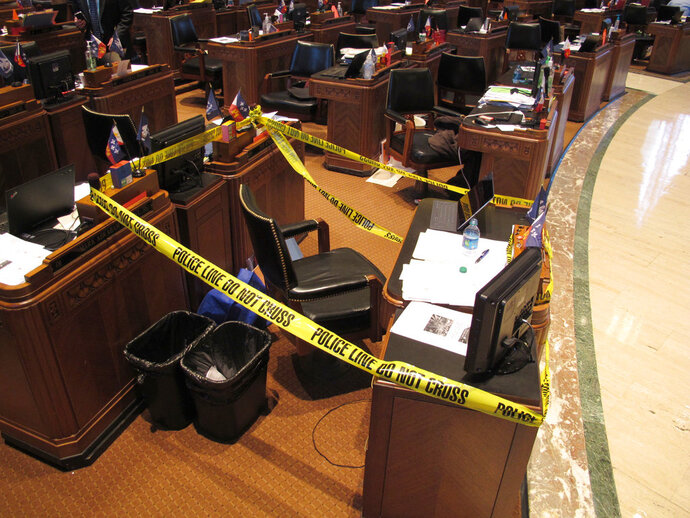 Lawmakers in the House roped off the area around Rep. Stuart Bishop's desk, on Wednesday, May 16, 2018, in Baton Rouge, La. The police tape was a joke after Bishop, R-Lafayette, got into a bar fight with Sen. Norby Chabert, a Houma Republican, a night earlier. Both say they regret the fight and consider themselves friends. (AP Photo/Melinda Deslatte)