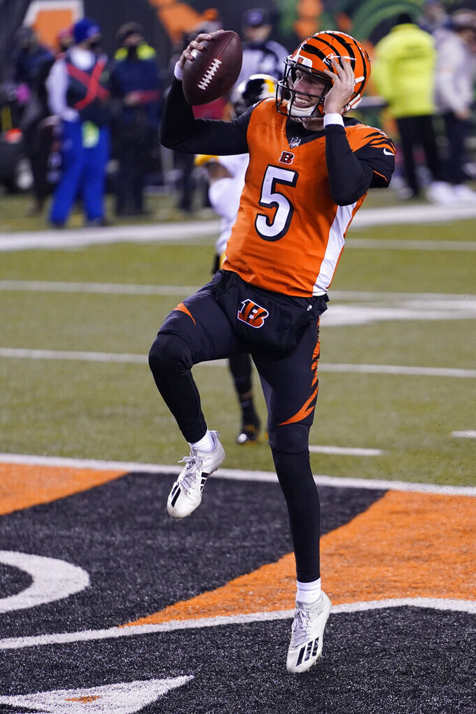 Cincinnati Bengals quarterback Ryan Finley reacts after running for a touchdown during the second half of an NFL football game against the Pittsburgh Steelers, Monday, Dec. 21, 2020, in Cincinnati. (AP Photo/Bryan Woolston)