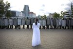 A woman wearing white, stands in front of a riot police line during a Belarusian opposition supporters' rally protesting the official presidential election results in Minsk, Belarus, Sunday, Sept. 13, 2020. Protests calling for the Belarusian president's resignation have broken out daily since the Aug. 9 presidential election that officials say handed him a sixth term in office. (TUT.by via AP)