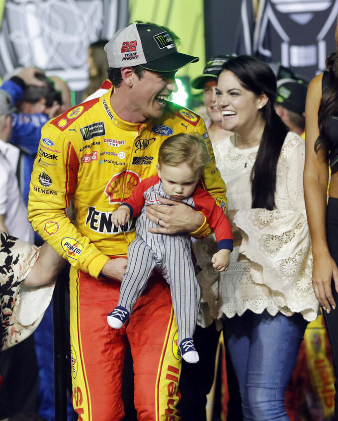 Joey Logano stands with his wife Brittany Baca, as he holds their son Hudson, after winning the NASCAR Cup Series Championship auto race at the Homestead-Miami Speedway, Sunday, Nov. 18, 2018, in Homestead, Fla. (AP Photo/Lynne Sladky)