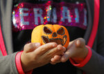 In this Saturday, Oct. 26, 2019 photo a child holds a carved pumpkin at The Halloween Pumpkin Fest in Bucharest, Romania. (AP Photo/Vadim Ghirda)