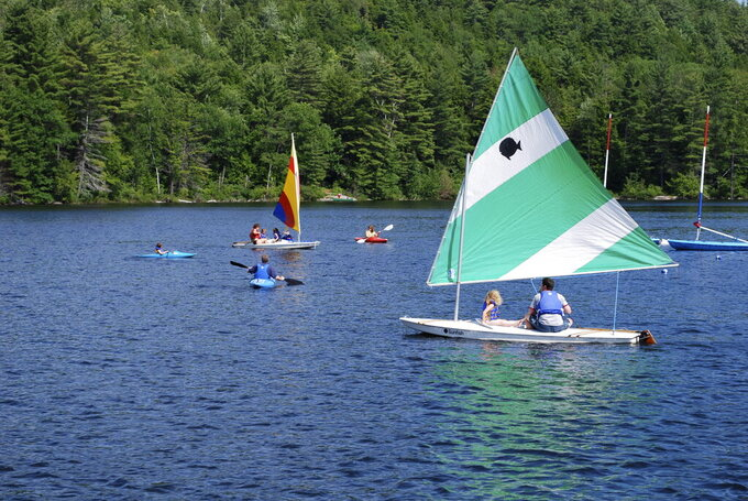 This image released by Forest Lake Camp shows campers boating and kayaking on the lake of the camp in Warrensburg, N.Y. Summer camps have begun to notify families that they won't open due to the coronavirus crisis. Most, however, are in wait-and-see mode as parents who rely on camp for child care as well as child fun try not to panic. (Forest Lake Camp via AP)