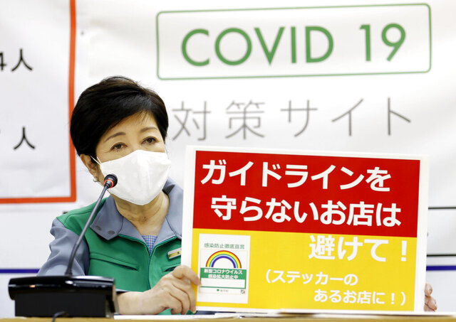 Tokyo Governor Yuriko Koike speaks during a press conference at the Metropolitan Government Office Wednesday, July 15, 2020, in Tokyo. Experts on Tokyo's coronavirus task force have raised caution levels for the infections in the Japanese capital to the highest on a scale of four, and urged officials to step up effort to secure more beds, increase testing capacities and raise awareness among the residents about the urgency. The placard reads