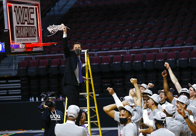Grand Canyon coach Bryce Drew holds up the net after the team defeated New Mexico State 74-56 in an NCAA college basketball game for the championship of the Western Athletic Conference men's tournament Saturday, March 13, 2021, in Las Vegas. (AP Photo/Chase Stevens)