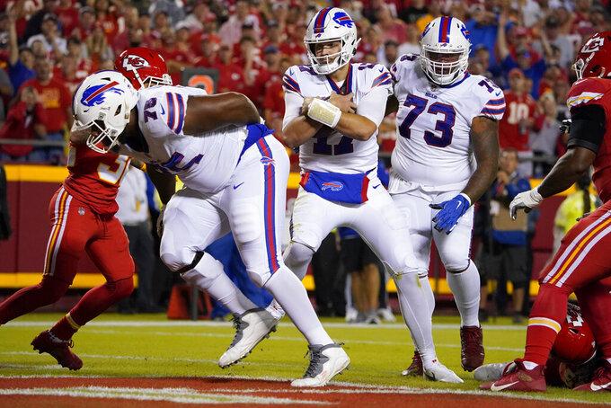 Buffalo Bills quarterback Josh Allen, center, scores on a touchdown run between teammates Daryl Williams (75) and Dion Dawkins (73) during the first half of an NFL football game Sunday, Oct. 10, 2021, in Kansas City, Mo. (AP Photo/Ed Zurga)