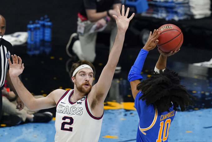 Gonzaga forward Drew Timme (2) tries to block a shot by UCLA guard Tyger Campbell (10) during the first half of a men's Final Four NCAA college basketball tournament semifinal game, Saturday, April 3, 2021, at Lucas Oil Stadium in Indianapolis. (AP Photo/Darron Cummings)