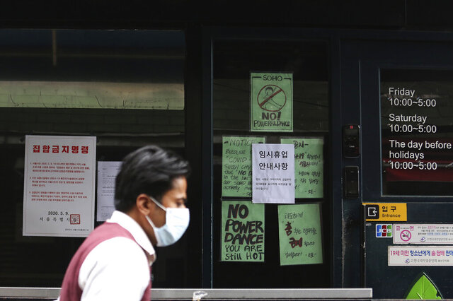 A man waring a face mask passes by notices at the entrance of a temporary closed dance club in Seoul, South Korea, Sunday, May 10, 2020. South Korea on Friday advised nightclubs and similar entertainment venues to close for a month and may delay the reopening of schools after linking more than a dozen new coronavirus infections to clubgoers in the capital. The signs read