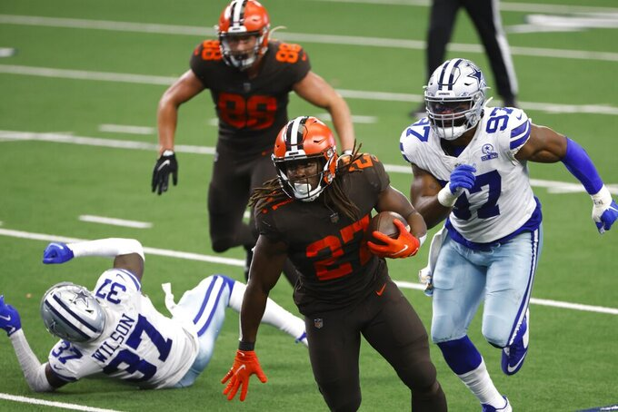 Cleveland Browns running back Kareem Hunt (27) sprints to the end zone for a touchdown as Dallas Cowboys' Donovan Wilson (37) and Everson Griffen (97) give chase in the second half of an NFL football game in Arlington, Texas, Sunday, Oct. 4, 2020. (AP Photo/Ron Jenkins)