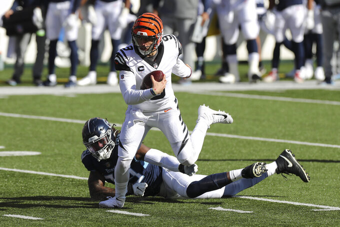 Cincinnati Bengals quarterback Joe Burrow (9) runs out of the tackle of Tennessee Titans' Jadeveon Clowney (99) during the first half of an NFL football game, Sunday, Nov. 1, 2020, in Cincinnati. (AP Photo/Jay LaPrete)