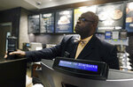 A plain-clothed police officer mans a position behind the counter at the Starbucks that has become the center of protests in Monday, April 16, 2018, in Philadelphia. The CEO of Starbucks arrived in Philadelphia hoping to meet with two black men who were arrested when the coffee chain's employees called 911 and said they were trespassing. Meanwhile, protesters took over the shop Monday. (AP Photo/Jacqueline Larma)
