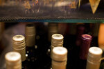 This Dec. 25, 2018, photo shows wine bottles at the bar at a bowling alley in Eagle, Colo. No one expects consumers to completely abandon Bordeaux wine from France, Scotch whisky or cheeses like Stilton, Roquefort when the tariffs take effect Friday, but retailers as well as their importers and distributors are aware that buying habits may change if shoppers fear they're now paying 25% more for their favorite drinks and delicacies. (AP Photo/Jenny Kane)
