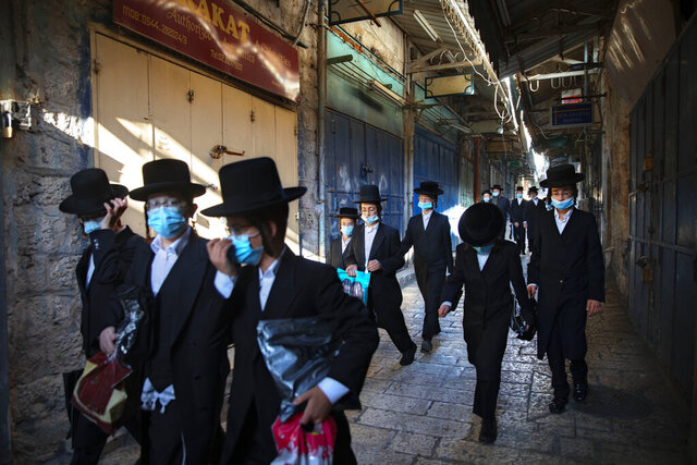 A group of ultra-Orthodox Jewish youth wear protective face masks following government measures to help stop the spread of the coronavirus, as they walk in Jerusalem's Old City, Thursday, July 16, 2020. (AP Photo/Oded Balilty)