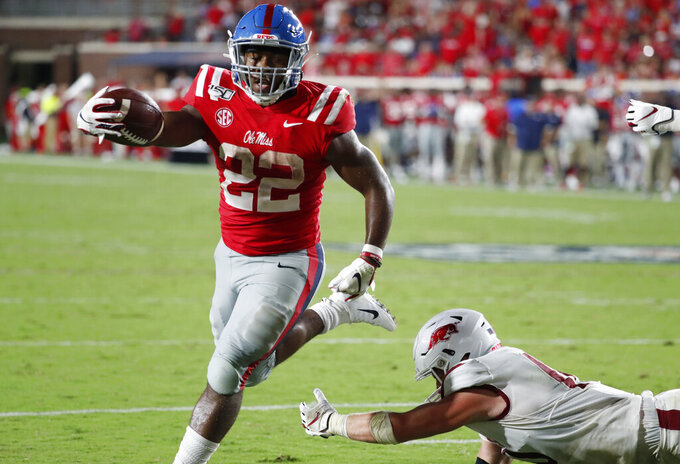 Mississippi running back Scottie Phillips (22) holds out his arm as he scores on a one-yard touchdown run past a fallen Arkansas defender during the second half of their NCAA college football game, Saturday, Sept. 7, 2019, in Oxford, Miss. Mississippi won 31-17. (AP Photo/Rogelio V. Solis)