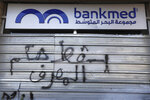 A door of a closed bank is spray painted with a message in Arabic that reads,