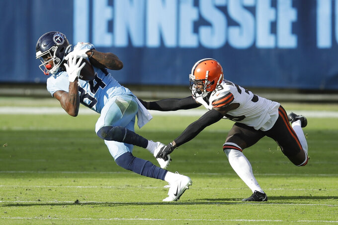 Tennessee Titans wide receiver Corey Davis (84) makes a catch as he is defended by Cleveland Browns cornerback Terrance Mitchell (39) in the second half of an NFL football game Sunday, Dec. 6, 2020, in Nashville, Tenn. (AP Photo/Ben Margot)