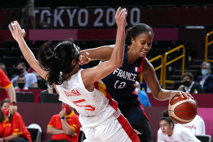 France's Iliana Rupert (12) drives around Spain's Cristina Ouvina (5) during a women's basketball quarterfinal round game at the 2020 Summer Olympics, Wednesday, Aug. 4, 2021, in Saitama, Japan. (AP Photo/Eric Gay)