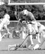 FILE - In this Nov. 14, 1977, file photo, New England Patriots fullback Sam Cunningham (39), seems to be taking off from the ground as Miami Dolphins linebacker Steve Towle (56) charges in for the tackle during an NFL football game in Miami. Cunningham, an All-American fullback at Southern California whose performance against Alabama was credited for helping integrate football in the Deep South before he went on to a record-setting career with the New England Patriots, died Tuesday, Sept. 7, 2021, at his home in Inglewood, Calif., according to USC. He was 71. (AP Photo/Phil Sandlin, File)