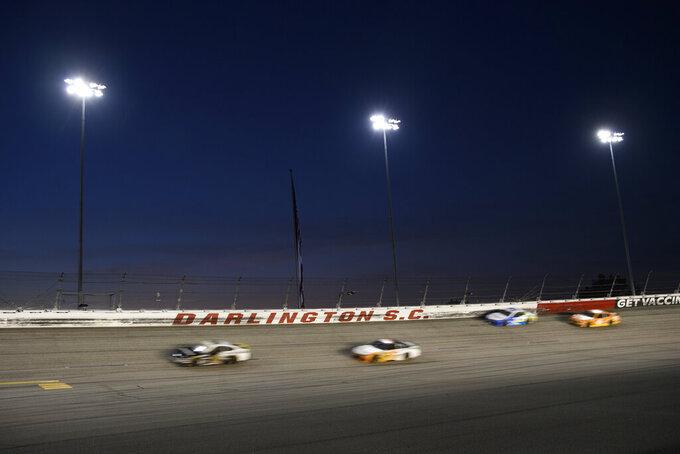 Cars race under the lights during a NASCAR Cup Series auto race Sunday, Sept. 5, 2021, in Darlington, S.C. (AP Photo/John Amis)