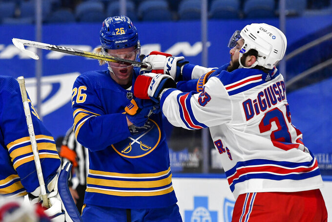 Buffalo Sabres defenseman Rasmus Dahlin (26) and New York Rangers left wing Phillip Di Giuseppe (33) exchange shoves after the whistle during the first period of an NHL hockey game in Buffalo, N.Y., Thursday, April 1, 2021. (AP Photo/Adrian Kraus)
