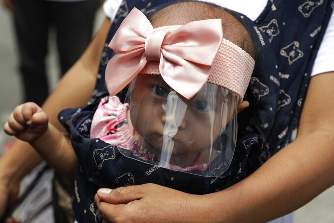 A 6-month-old baby wears a face shield to help protect herself from the coronavirus in Manila, Philippines, Friday, March 19, 2021. The Department of Health reported over 7000 new COVID-19 cases today, the highest number since the pandemic hit the country last year as it struggles to contain an alarming surge in coronavirus infections. (AP Photo/Aaron Favila)