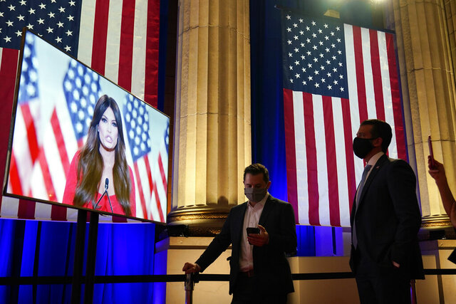 Donald Trump Jr., right, watches as his girlfriend Kimberly Guilfoyle, tapes her speech for the first night of the Republican National Convention from the Andrew W. Mellon Auditorium in Washington, Monday, Aug. 24, 2020. (AP Photo/Susan Walsh)