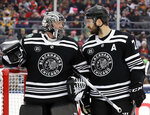 Chicago Blackhawks defenseman Brent Seabrook, right, talks to goalie Cam Ward in the first period of the NHL Winter Classic hockey game against the Boston Bruins at Notre Dame Stadium, Tuesday, Jan. 1, 2019, in South Bend, Ind. (AP Photo/Nam Y. Huh)