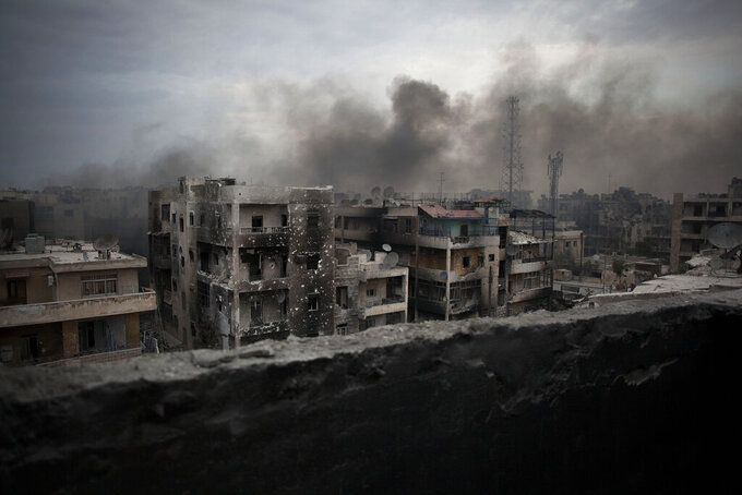 FILE - In this Oct. 2, 2012 file photo, smoke rises over Saif Al Dawla district, in Aleppo, Syria. Syrians are marking 10 years since peaceful protests against President Bashar Assad's government erupted in March 2011, touching off a popular uprising that quickly turned into a full-blown civil war. (AP Photo/ Manu Brabo, File)